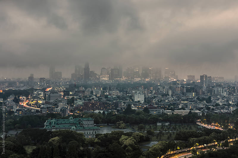 Fog and Clouds over Shinjuku Skyline as Seen from Central Tokyo at Dusk by Tom Uhlenberg for Stocksy United