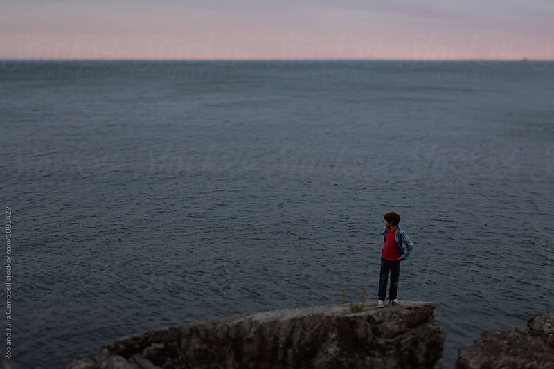 Young preteen caucasian boy outside in nature - standing on rock by Rob and Julia Campbell for Stocksy United