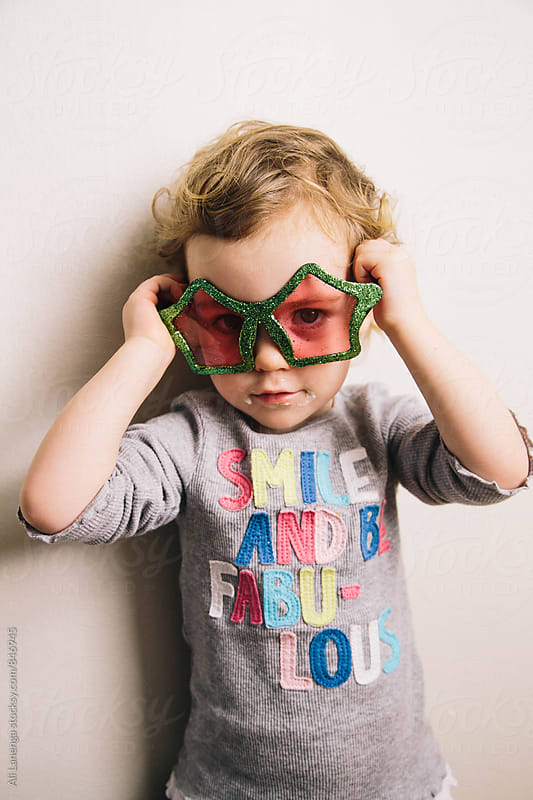 Child wearing sparkle glasses by Ali Lanenga for Stocksy United