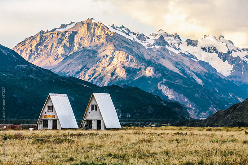 Mountain view with small houses or huts at sunset on Patagonia by Alejandro Moreno de Carlos for Stocksy United
