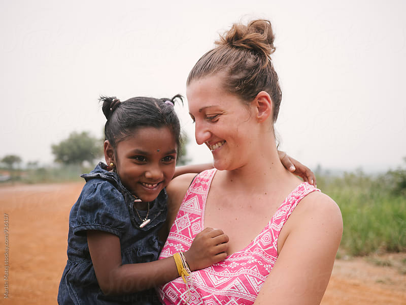 Joyful mother smiling at her adopted indian daughter by Martin Matej for Stocksy United