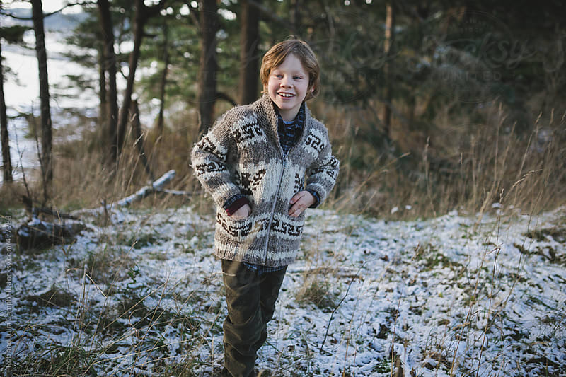 Happy young boy smiling outside in winter by Rob and Julia Campbell for Stocksy United