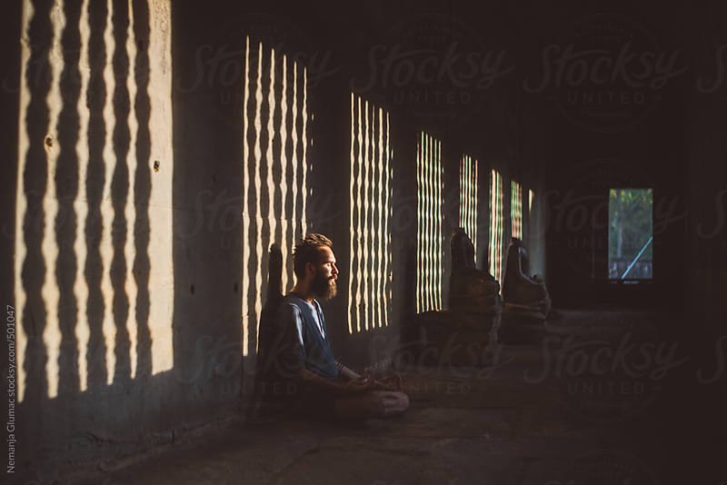 Man With Beard Meditating in Angkor Wat With the Last Rays of Setting Sun by Nemanja Glumac for Stocksy United