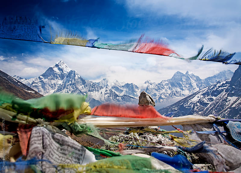 Snow-capped Himalayan mountain range viewed through flying tibetan prayer flags  by Dejan Ristovski for Stocksy United