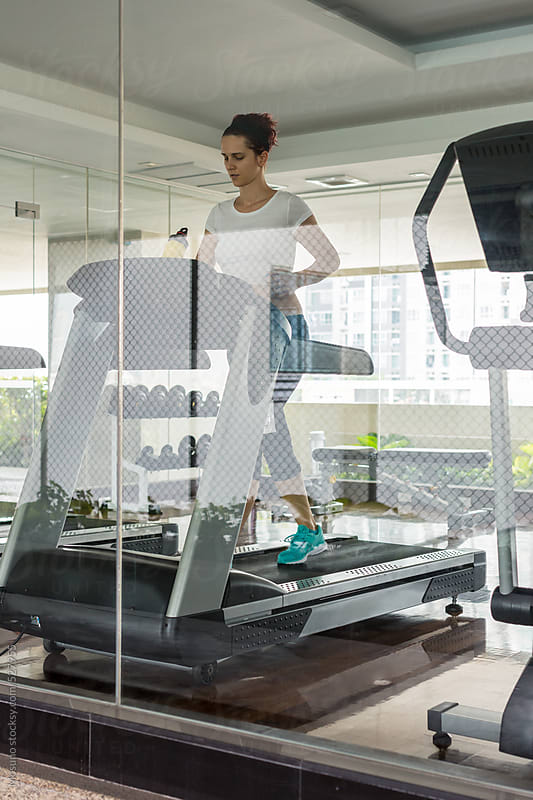 Young Caucasian Woman Running on a Treadmill by Mosuno for Stocksy United
