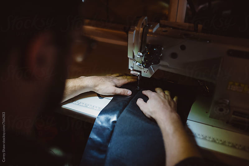 Man using sewing machine in workshop by Carey Shaw for Stocksy United