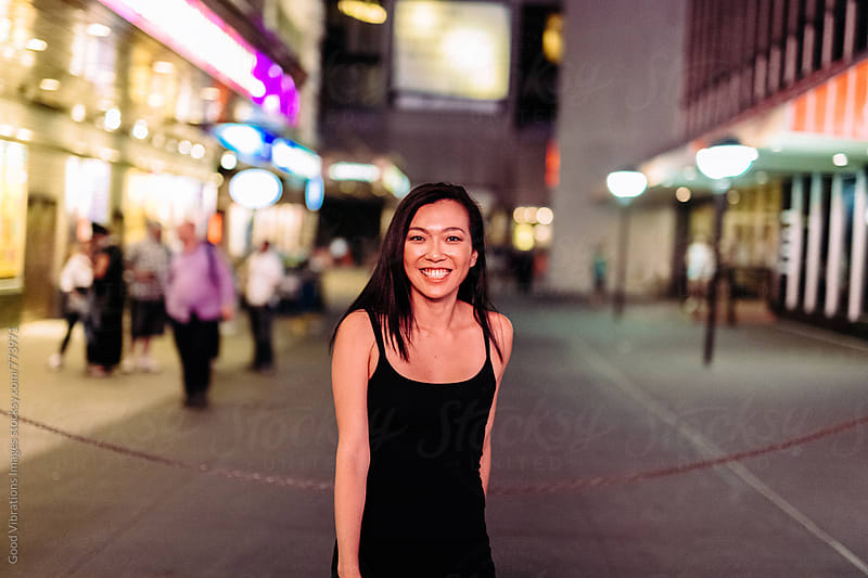 Asian woman having fun outdoors at night by Good Vibrations Images for Stocksy United