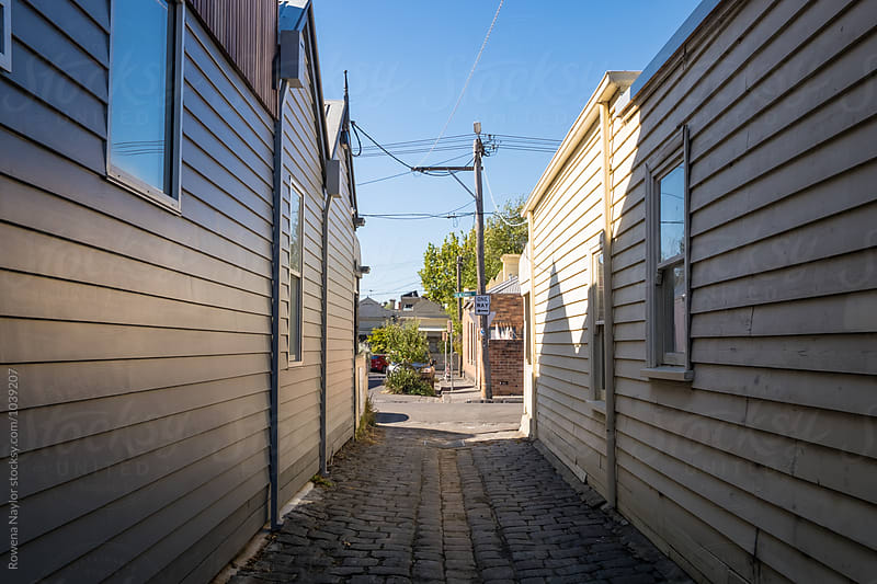 Looking through laneway between two timber homes by Rowena Naylor for Stocksy United