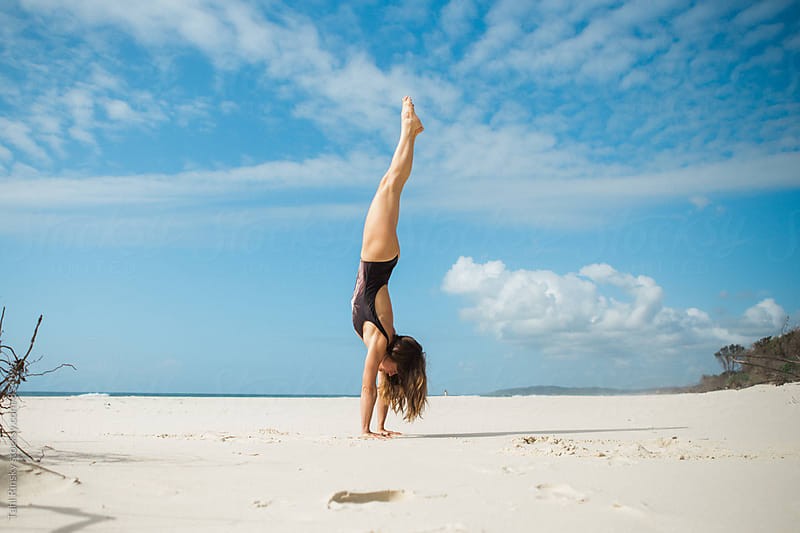 women doing handstand on beach in bathing suit  by Tahl Rinsky for Stocksy United