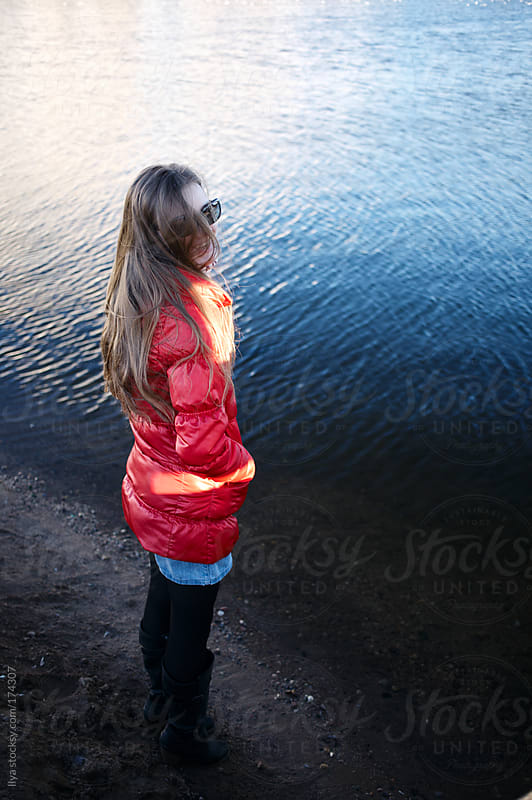 Young woman standing on lake coast by Ilya for Stocksy United
