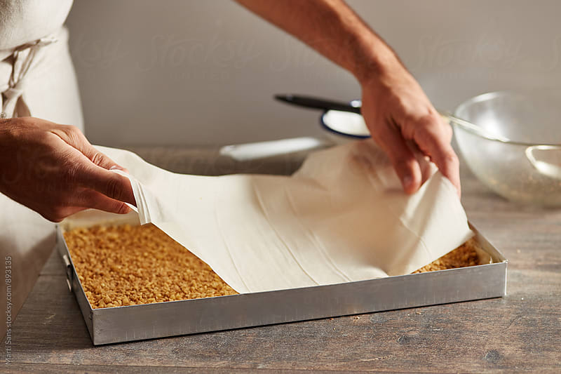 Chef placing phyllo sheet into baking pan by Martí Sans for Stocksy United