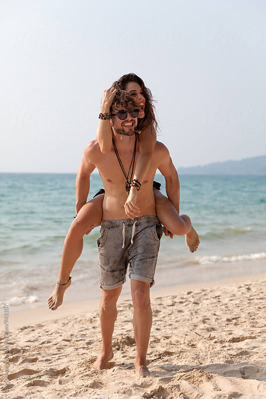 Man carrying woman - vacation happiness by Jovo Jovanovic for Stocksy United