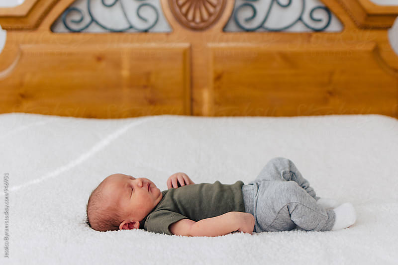 Newborn baby boy lying on parents' bed. by Jessica Byrum for Stocksy United