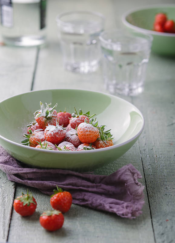 A bowl of strawberry's with a dusting of icing sugar. by Darren Muir for Stocksy United