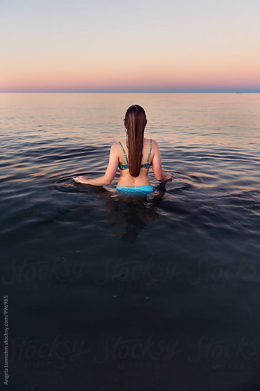 Girl viewed from behind standing in calm water at the beach at sunset by Angela Lumsden for Stocksy United