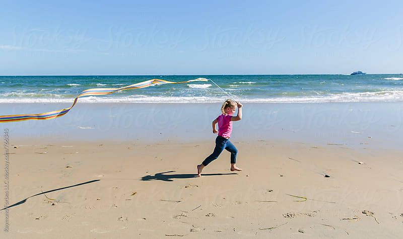 Child Running on Beach with Wand by Raymond Forbes LLC for Stocksy United