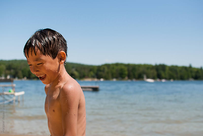 young boy laughs near a lake by Margaret Vincent for Stocksy United