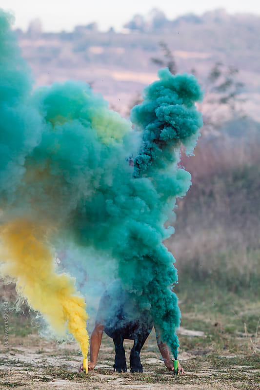 yellow and green,person with two smoke bombs  in nature by Igor Madjinca for Stocksy United