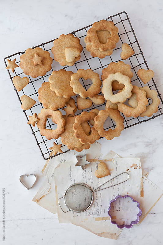 Hand written recipes with cookie cutters and various shapes of baked cookies by Nadine Greeff for Stocksy United