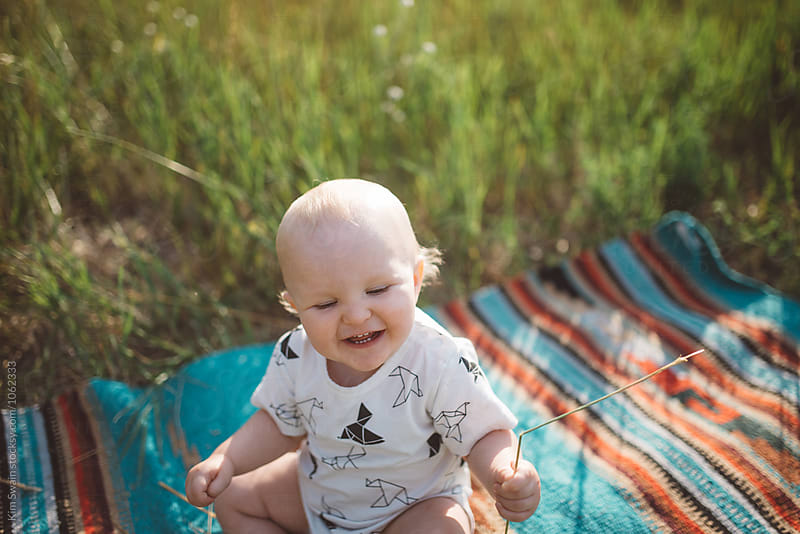 Baby Laughing in Field by Kim Swain for Stocksy United