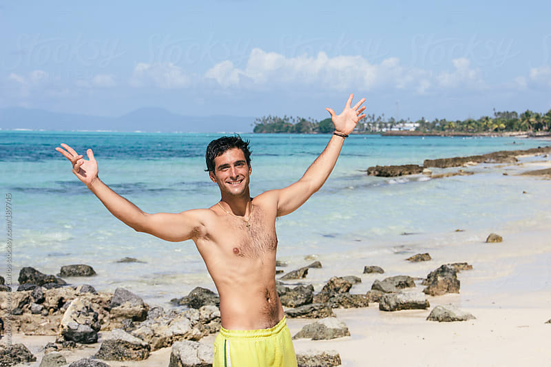 Young happy man with swimsuit on the beach in tropical island by Alejandro Moreno de Carlos for Stocksy United