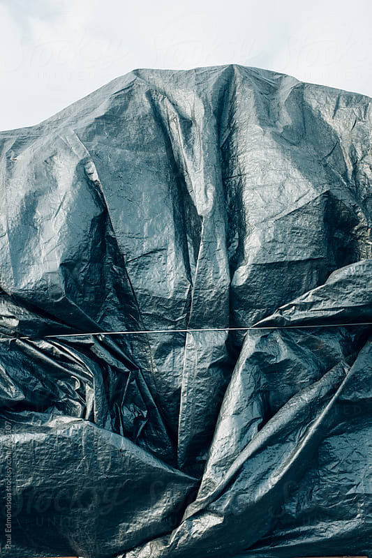 Silver tarpaulin covering pile of commercial fishing equipment
