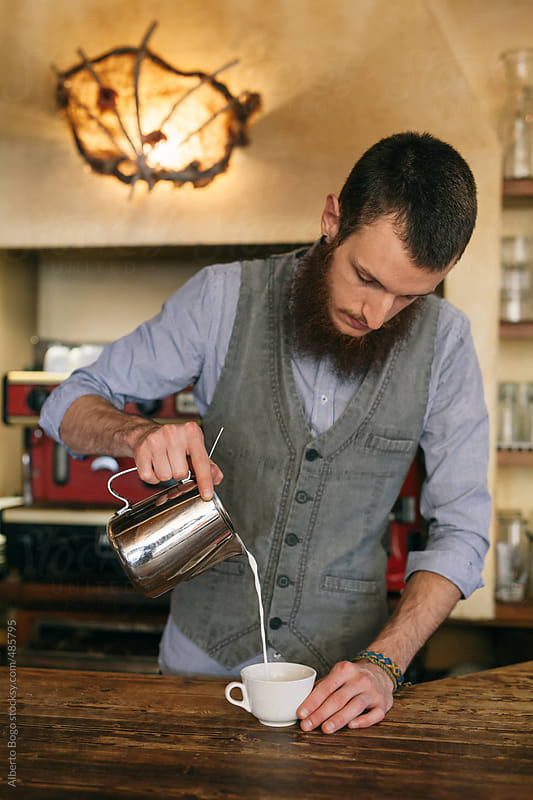 young man barista making coffee by Alberto Bogo for Stocksy United