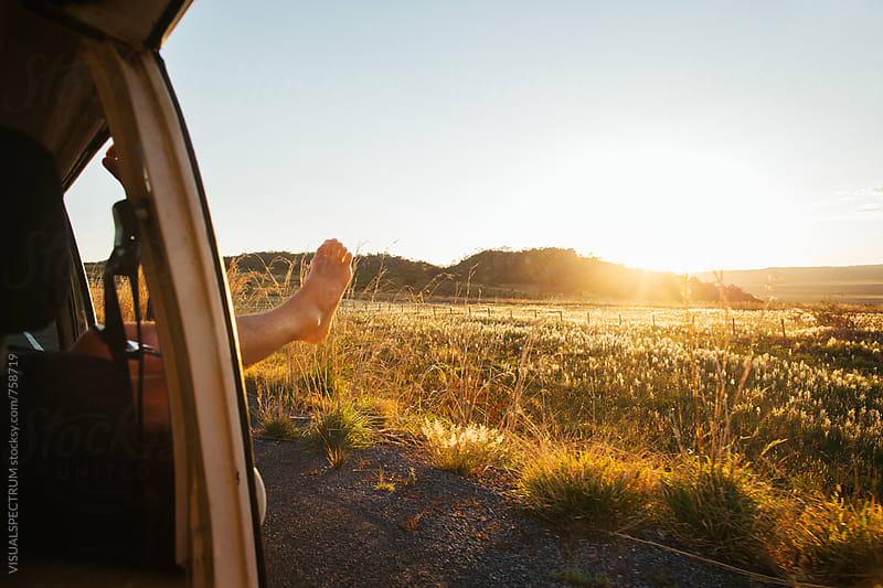Road Tripping - Man Stretching His Leg Outside Window While Driving at Sunset Time by Julien L. Balmer for Stocksy United