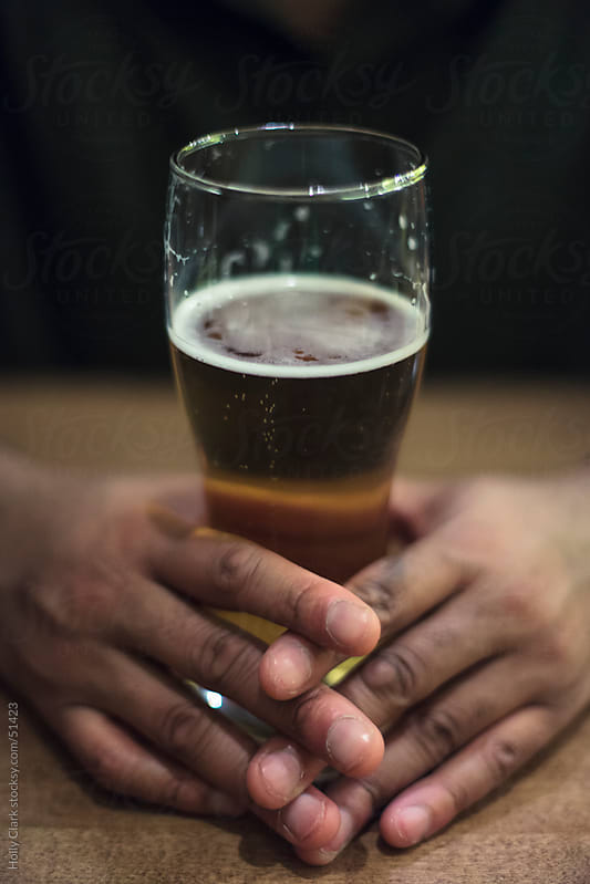 African-American man's hands holding a glass of beer on a table. by Holly Clark for Stocksy United