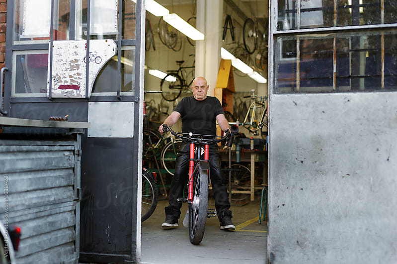 Senior adult bicycle mechanic on test ride by VegterFoto for Stocksy United