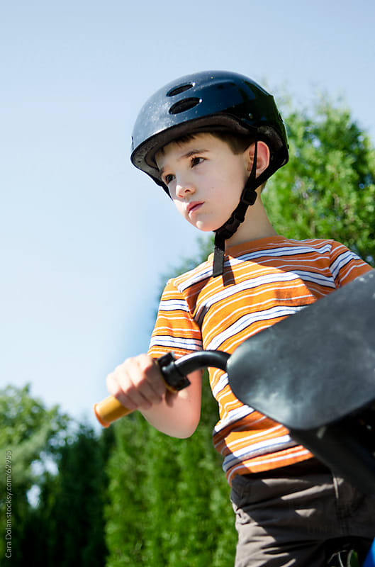 Boy on bicycle wearing helmet  by Cara Dolan for Stocksy United