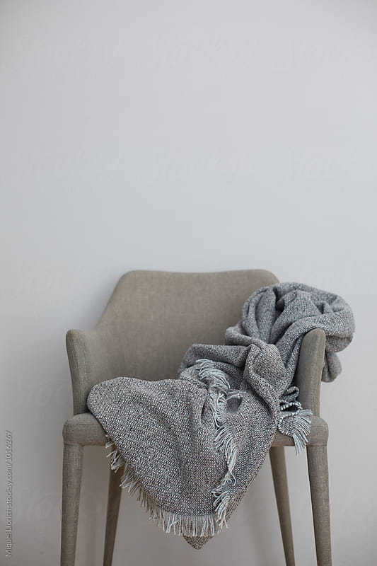 Unfolded grey blanket on a chair by Miquel Llonch for Stocksy United