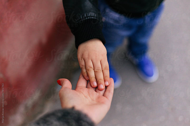 Female hand holding a hand of a little boy by Marija Kovac for Stocksy United