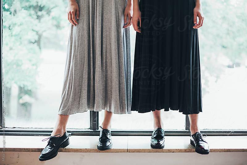 Two beautiful models in dresses standing near a window by Maja Topcagic for Stocksy United