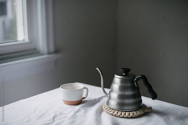 Kettle and white mug for tea on white table cloth by Daring Wanderer for Stocksy United
