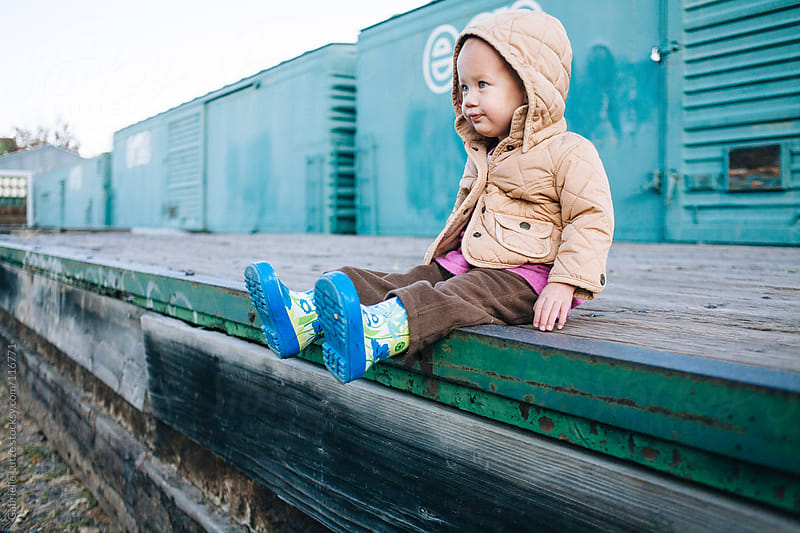 Cute little Girl Sitting by a Train by Gabrielle Lutze for Stocksy United
