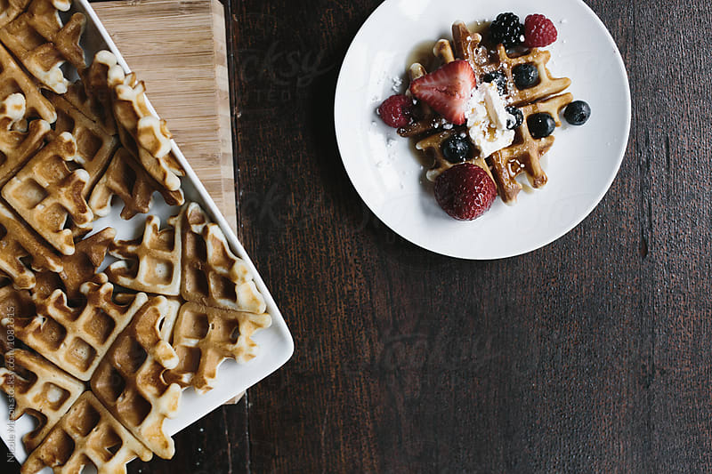 tray of waffles beside plate of waffle and berries by Nicole Mason for Stocksy United