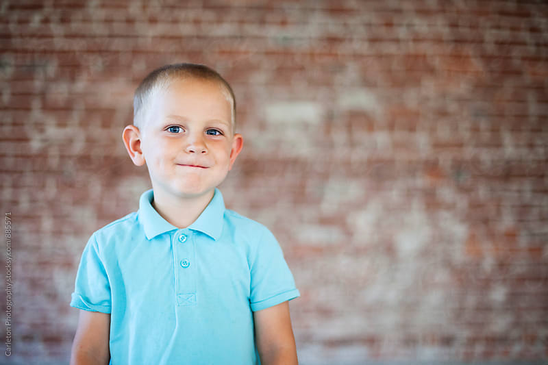 Torso up portrait of boy in blue polo in front of brick wall by Carleton Photography for Stocksy United