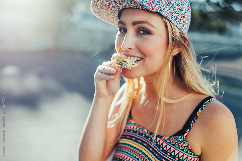 Beautiful young woman eating pizza by Jacob Lund for Stocksy United