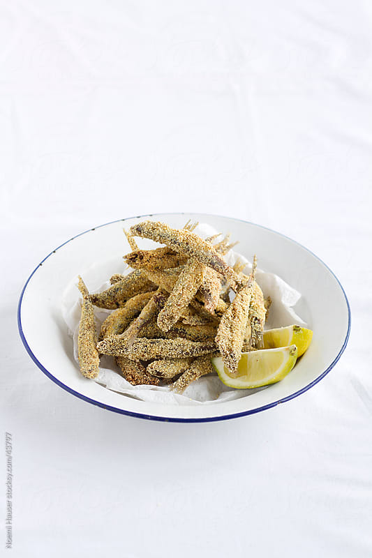 Deep fried anchovies on plate with lemon wedges  by Noemi Hauser for Stocksy United