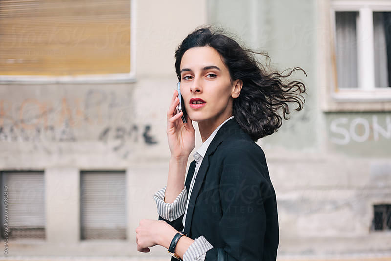 Beautiful brunette woman talking on the phone in the street by Marija Mandic for Stocksy United