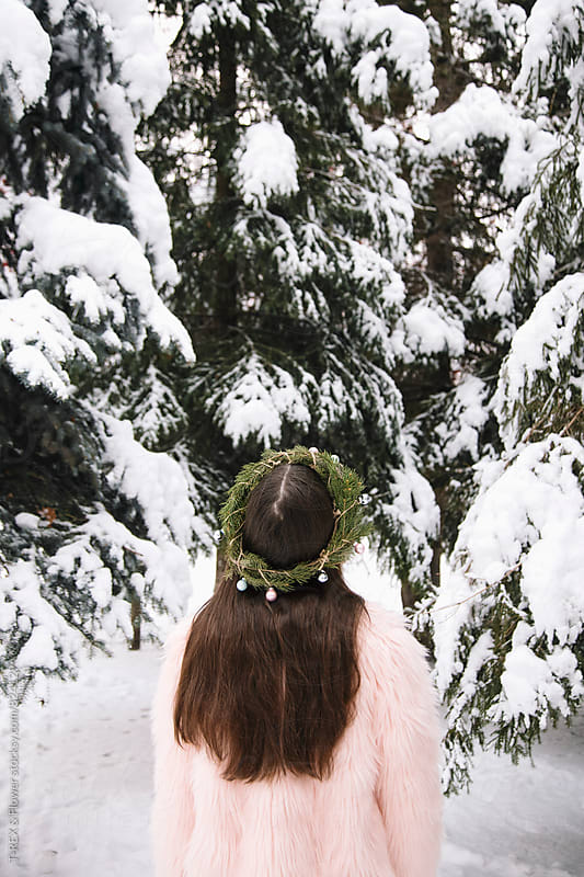 Back view of young woman in Christmas wreath looking up on snowy fir trees by Danil Nevsky for Stocksy United