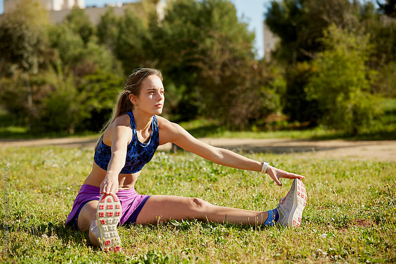 Determined Woman Stretching On Grass In Park by ALTO IMAGES for Stocksy United