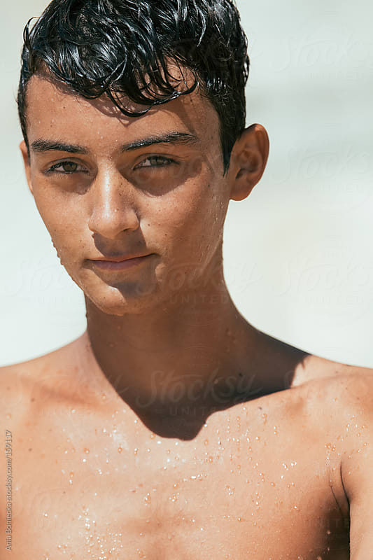 A portrait of a handsome young surfer dripping water after a swim by Ania Boniecka for Stocksy United