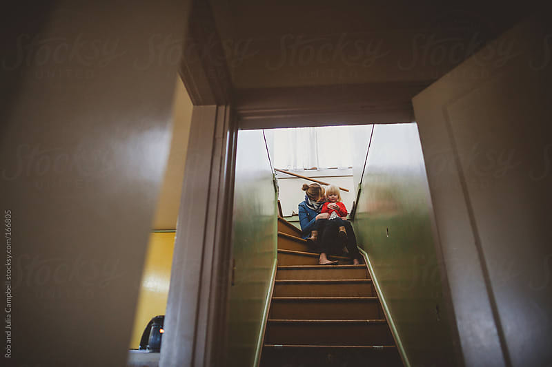 Young mom cuddling toddler girl on old stairs by Rob and Julia Campbell for Stocksy United
