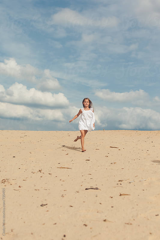 Barefoot little girl in a white dress running in the sand by Cindy Prins for Stocksy United