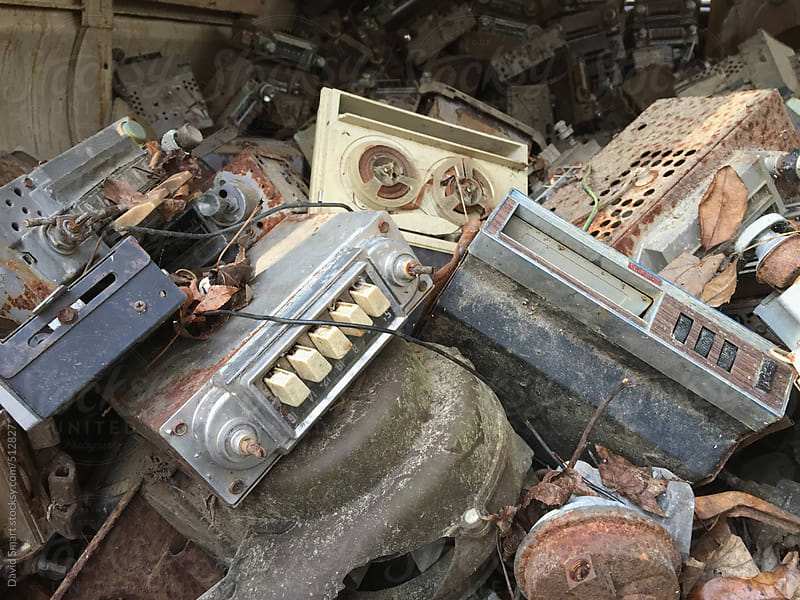 Old car radios and tape players on a junk heap by David Smart for Stocksy United