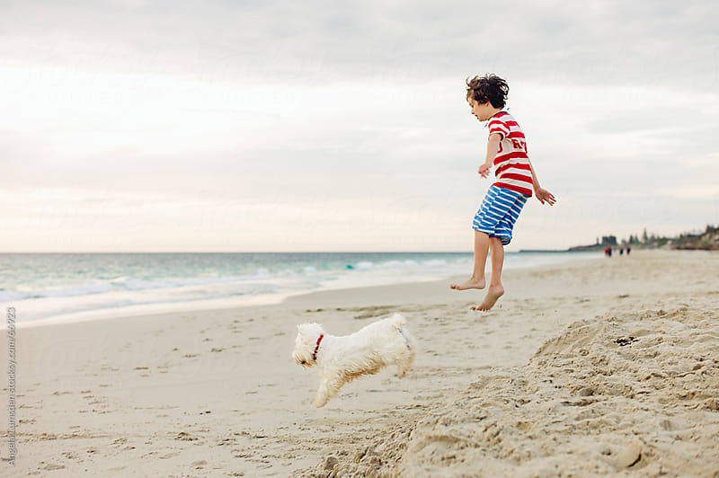 Boy and dog leaping together at the beach by Angela Lumsden for Stocksy United