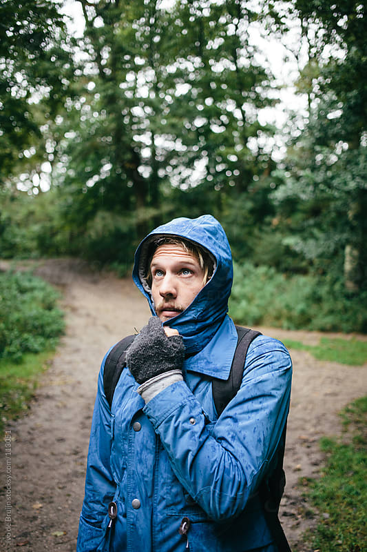 Young man looking up and disliking the weather in the forest by Ivo de Bruijn for Stocksy United