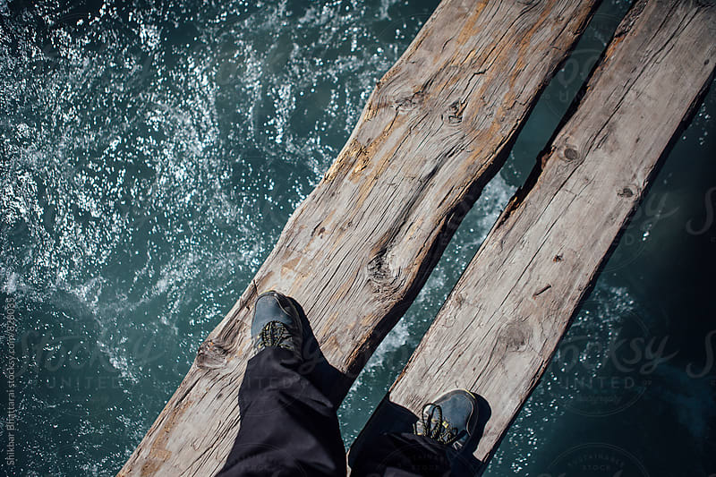 Looking down and crossing a wooden bridge. by Shikhar Bhattarai for Stocksy United